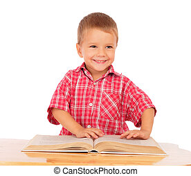 Smiling little boy reading book on the desk, isolated on white