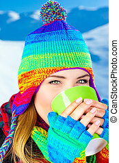 Beautiful girl drinking hot chocolate outdoor in winter,...