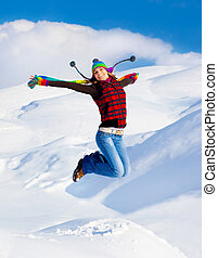 Happy girl jumping over blue sky and snow background, teen...