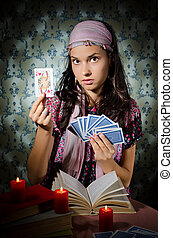 Fortune-teller predicing the cards - Young mystical woman...