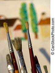 Paintbrushes and painted canvas in the background