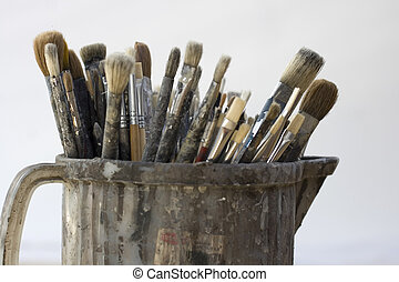 Paintbrushes inside a old jug