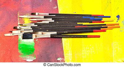 Paintbrushes on colorful background