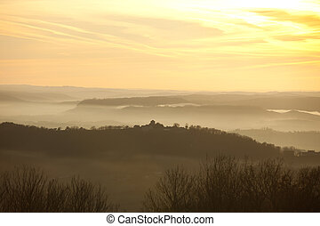 misty hills - Misty hills and village silhouette in the...