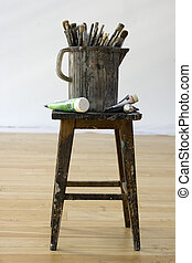 Paintbrushes and colors tubes on a stool