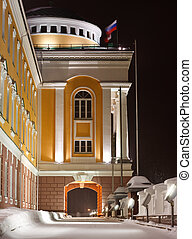 office building with an arch and flags at the night