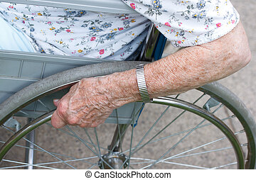 Seniors hand on wheel of wheelchair outside