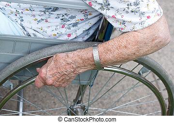 Senior's hand on wheel of wheelchair