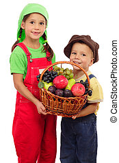 Two little children with basket of fruits, isolated on white