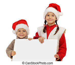 Little children in Christmas hats with an empty banner in...