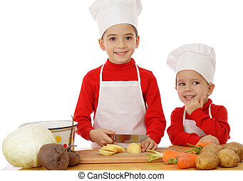 Smiling little chief-cookers on the desk with vegetables, isolated on white