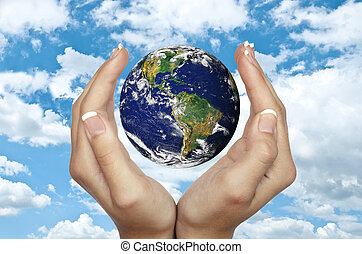 Human hands holding planet Earth against blue sky -...