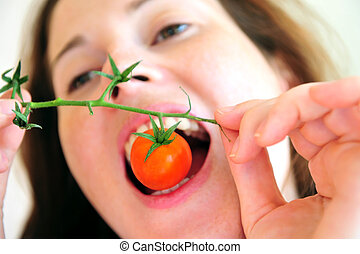 Fresh Tomatoes - Woman eats a cherry tomato from the vine.