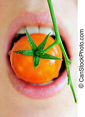 Fresh Tomatoes - Woman eats a cherry tomato from the vine