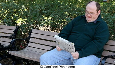 Man Reading Newspaper - Overweight man sits on a park bench...
