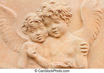 two angels holding together - terracotta relief