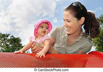 Baby Girl Plays with Mum in Playground - A little six month...