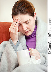 sick woman covered with blanket at home - A young sick woman...