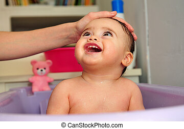 Cute Baby Bathtime - Cute baby is being washed in a purple...