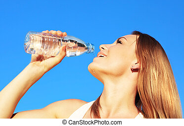 Drinking water - Beautiful female drinking water over blue...