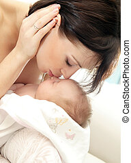 Happy mother with a baby - Happy young mother kissing a baby