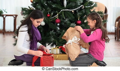 Unwrapping gifts - Girls unwrapping Christmas gifts