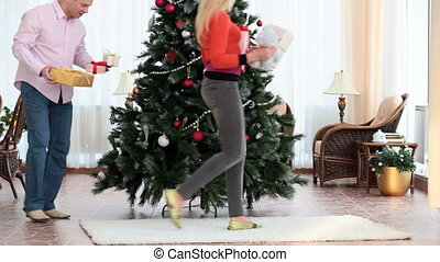 Putting gifts under fir-tree