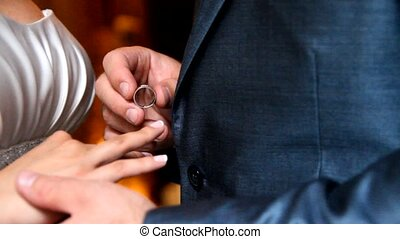 Groom putting a wedding ring on brides finger