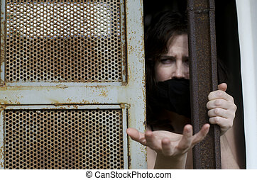 Trapped Woman - A woman trapped in a prison jail cell with a...