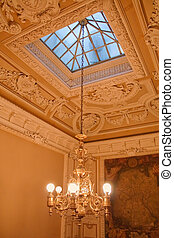 Chandelier hanging under a ceiling. Interiors of the Polovtsov mansion - Architect's house, St.Petersburg, Russia