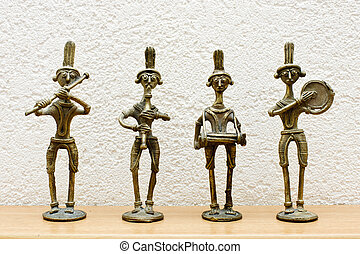 four African statues against the wall