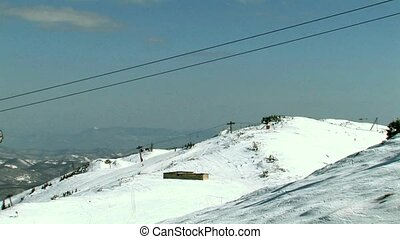 Six seat ski lift passing by with s