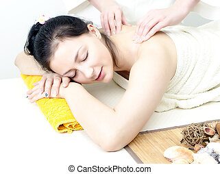 Young lady receiving back massage at spa center