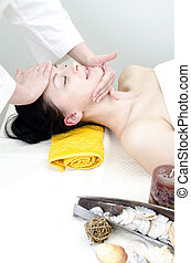Young lady receiving face massage at spa center