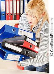 Hard working blond woman with lots of files