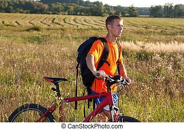 Man traveler cyclist with a bicycle and backpack in nature