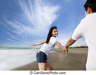 happy asian couple running on the beach