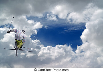 Freestyle ski jumper with crossed skis against blue sky with...