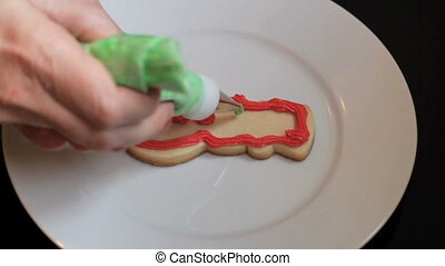 Snowman Shaped Christmas Cookie - A girl carefully adds...