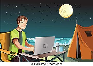 Man camping using laptop