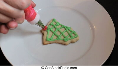 Red Icing On Christmas Cookie - A girl carefully adds red...