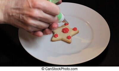 Finishing Touches Christmas Cookie - A girl carefully adds...