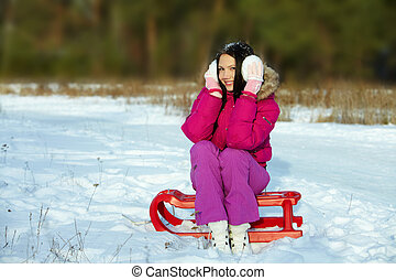 At leisure - Portrait of happy girl sitting on sledge and...