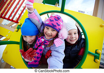 Cheerful friends - Happy kids in winterwear looking at...