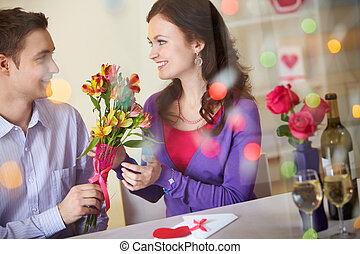 Romantic time - A young man giving floral bouquet to pretty...