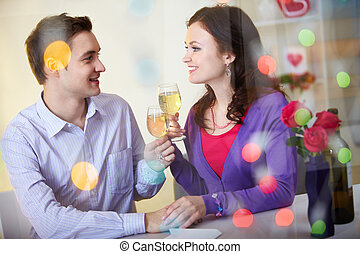 Celebrating Valentine day - A young happy couple sitting in...