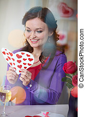 Valentine day - A young girl in restaurant holding Valentine...