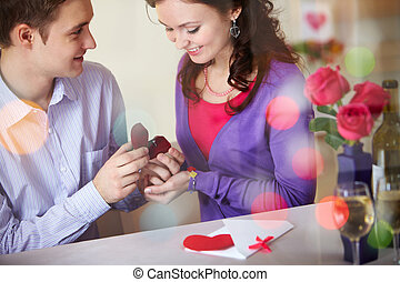 Engagement - A young man presenting engagement ring to his...