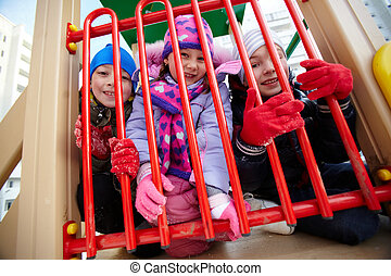 Friends on playground - Happy kids in winterwear looking at...