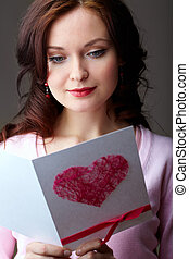 Girl reading card - Portrait of young woman holding...